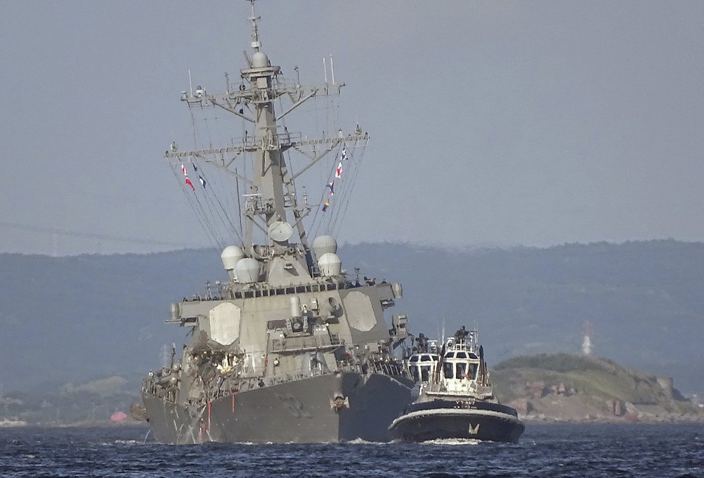 Tugboats guide the damaged USS Fitzgerald through waters near the U.S. naval base in Yokosuka, Japan. The destroyer collided on June 17 with the Philippine-registered container ship ACX Crystal, a much larger vessel. The guided-missile destroyer was built at Bath Iron Works and commissioned in 1995.