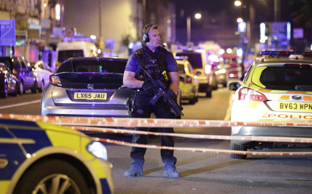 An armed police officer mans a cordon on the Seven Sisters Road at Finsbury Park, where a vehicle struck pedestrians in London early Monday.