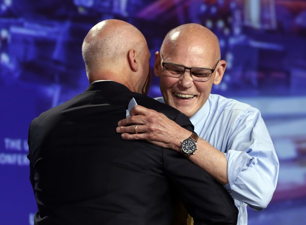 Political consultant James Carville, right, hugs New Orleans Mayor Mitch Landrieu following a speech at the annual U.S. Conference of Mayors meeting Monday in Miami Beach, Fla.