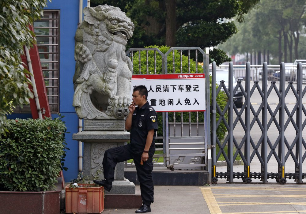 A security guard smokes near a main entrance gate of the Ganzhou Huajian International Shoe City Co.'s factory, which has made shoes for the brand owned by Ivanka Trump, left. The firm, located in Ganzhou, has denied abuse allegations, and Trump has not replied to a letter from China Labor Watch..
