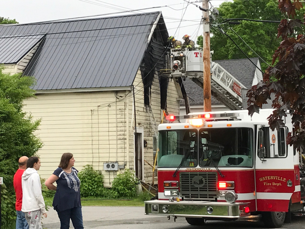 Officials work at the scene of a home fire Thursday morning on Spruce Street in Waterville, displacing six adults and two children.