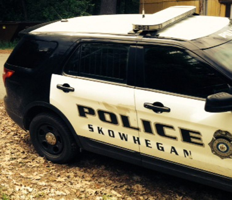 A Skowhegan police cruiser stands parked on Prescelly Drive in Skowhegan near the spot where a body was found Saturday in the woods.