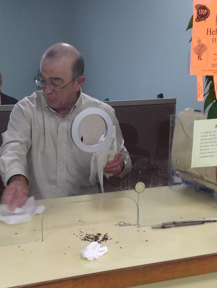 Ralph St. Pierre, Augusta's finance director and assistant city manager, picks up bed bugs that were reportedly spilled by a disgruntled man Friday afternoon at Augusta city hall.