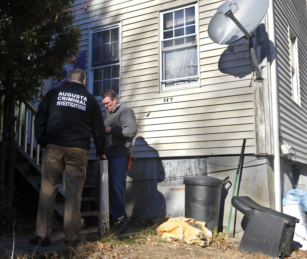 Augusta police Lt. Chris Massey, left, and Augusta Code Enforcement Officer Robert Overton inspect the apartment building at 117 Bridge St. in Augusta in 2016 after police executed a search warrant at the building and arrested two people on drug trafficking charges. The city now owns the property, which is next door to one that the council voted Thursday to purchase.