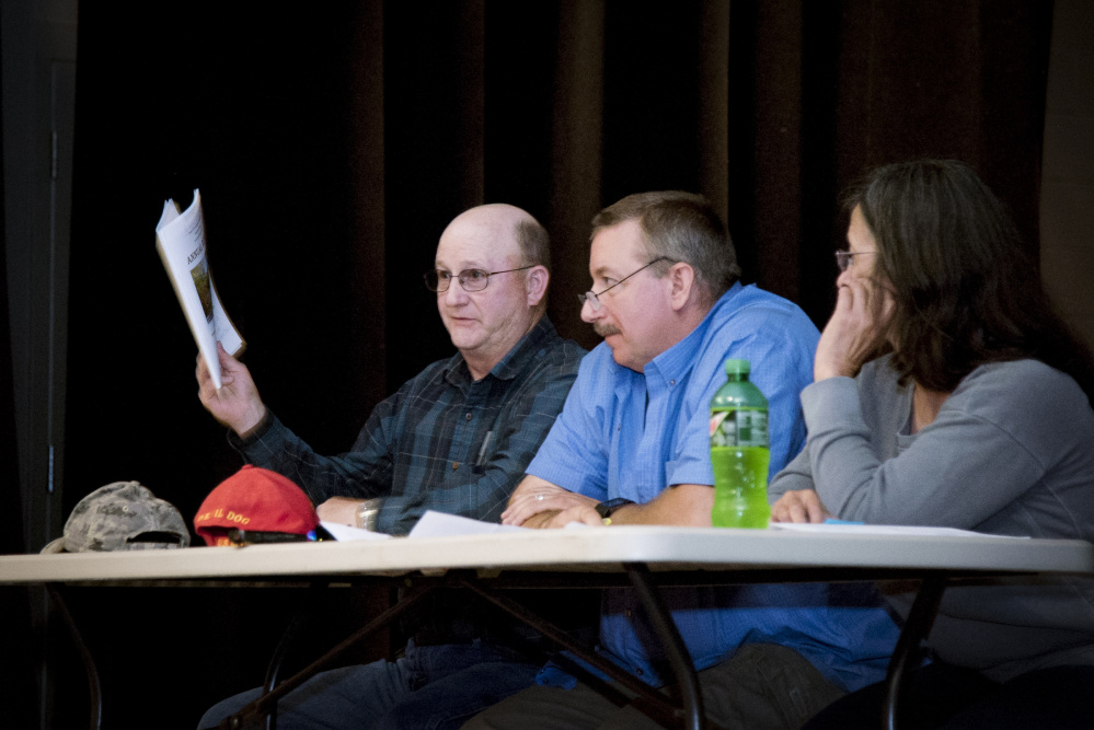 Selectman Wayne Kilgore, left, holds up the town warrant Saturday at Farmingdale's Town Meeting, while Selectman James Grant and Selectwoman Nancy Frost watch the proceedings.