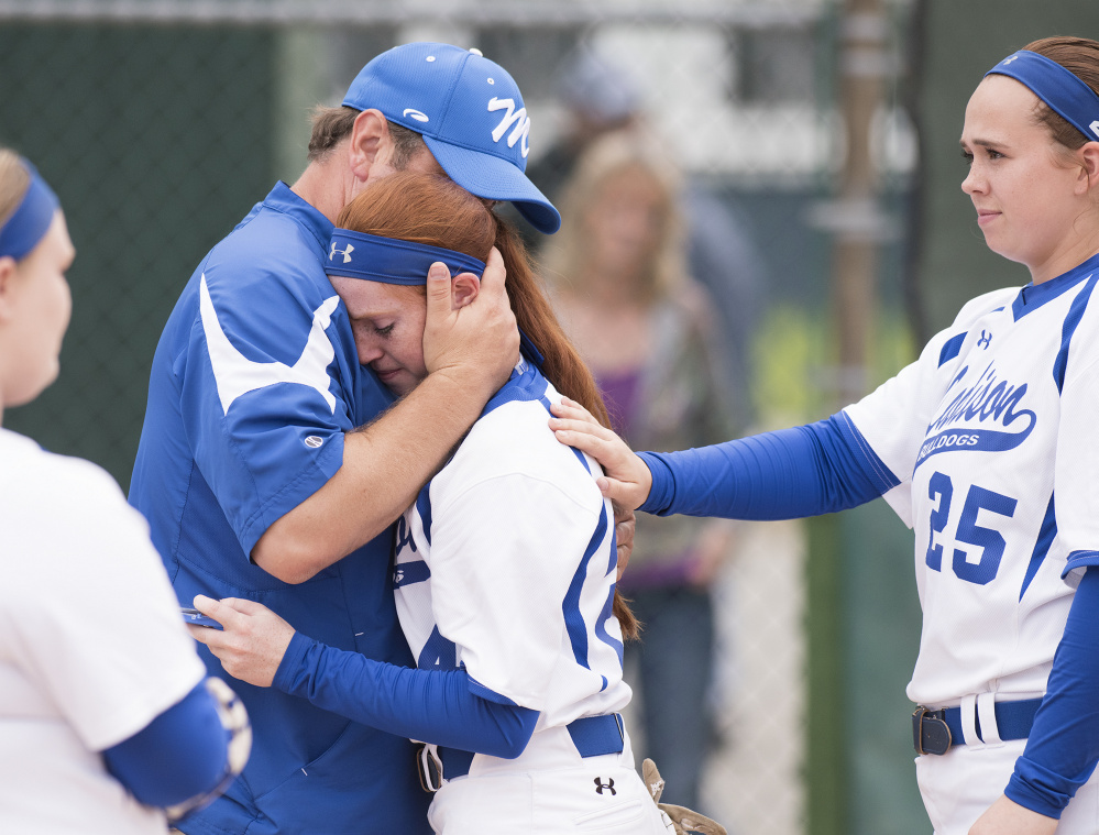 Kevin Bennett photo   Madison's Ashley Emery is comforted by head coach Chris LeBlanc and teammate Victoria Blauvet after losing to Bucksport in the Class C state championship Saturday in Brewer.