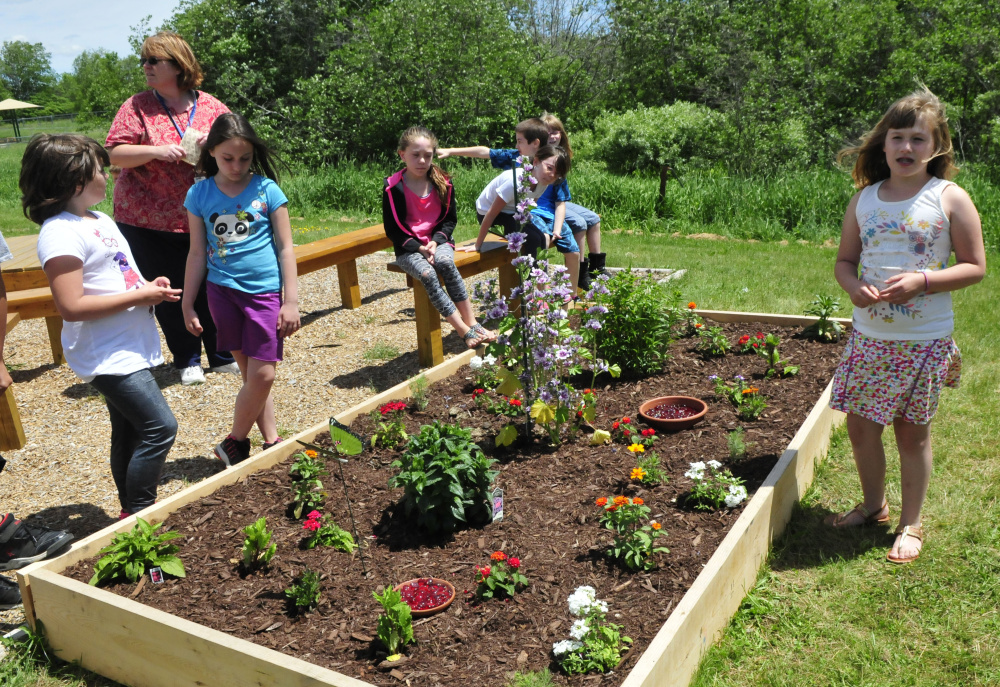 Bloomfield Elementary School student Gabby Goding explains how the class used donated materials and plants to create a garden to attract butterflies at the Skowhegan school Wednesday as teacher Lori Swenson looks on.