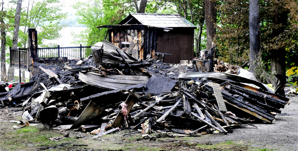 This cottage on Brickett Point Road on East Pond in Oakland was destroyed by fire Saturday. Neighbor Linda Cormier heard a popping noise that she believes were the windows exploding and when she went outside saw the home covered in fire.