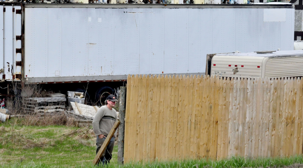 Robert Dale, owner of 201 Antiques, watches as another man, not visible in the photo, erects a fence around used merchandise in the front of the Fairfield business in May.