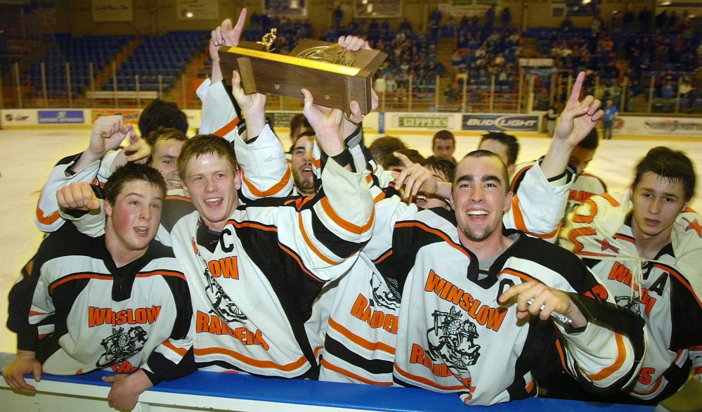 Winslow Raiders celebrate with their trophy after beating York 4-3 in overtime to win the class B state hockey championship on Saturday at The Colisee in Lewiston.