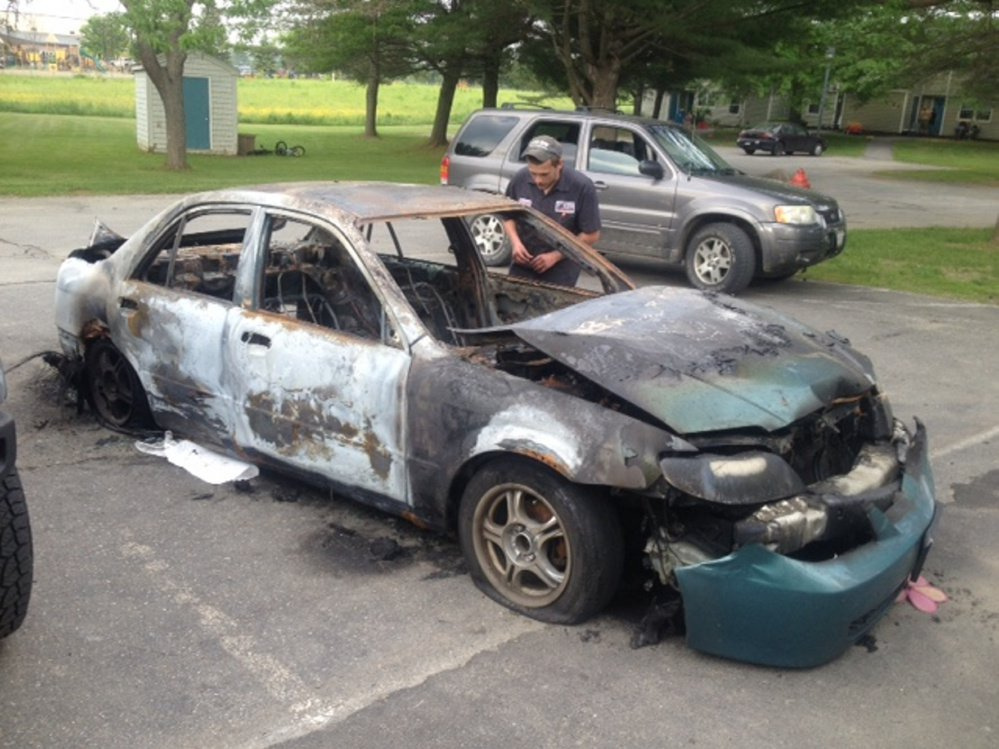Quincy McLaughlin, of Family Circle in Skowhegan, looks over his 2001 Mazda Protege, which was consumed by fire June 12. A 15-year-old boy has been charged with arson in connection with the setting of four car fires in Skowhegan.