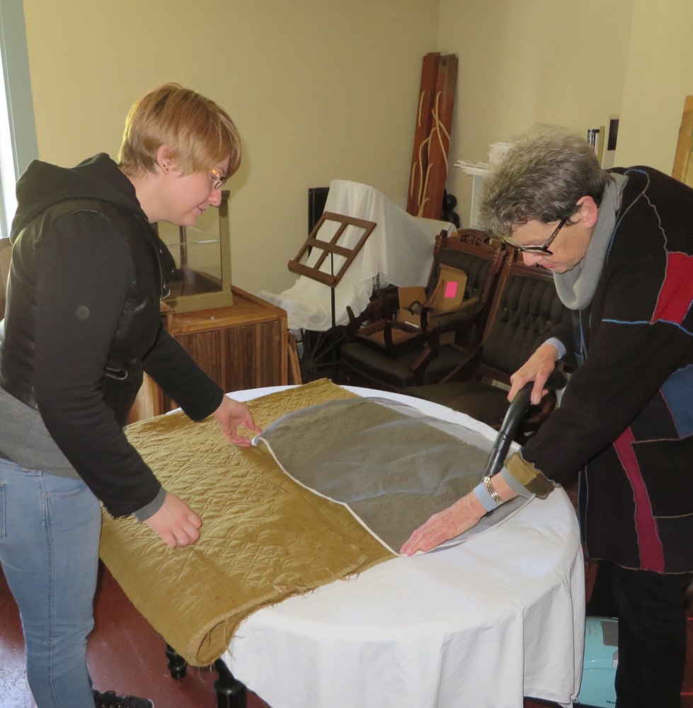 Katie Likens, left, a graduate student at the University of Rhode Island, and JoAnn Stabb, professor emerita, University of California at Davis, use a special vacuum to clean one of Lincoln County Historical Association's 18th century quilts with a special vacuum. The soft mesh screen prevents fibers from breaking.