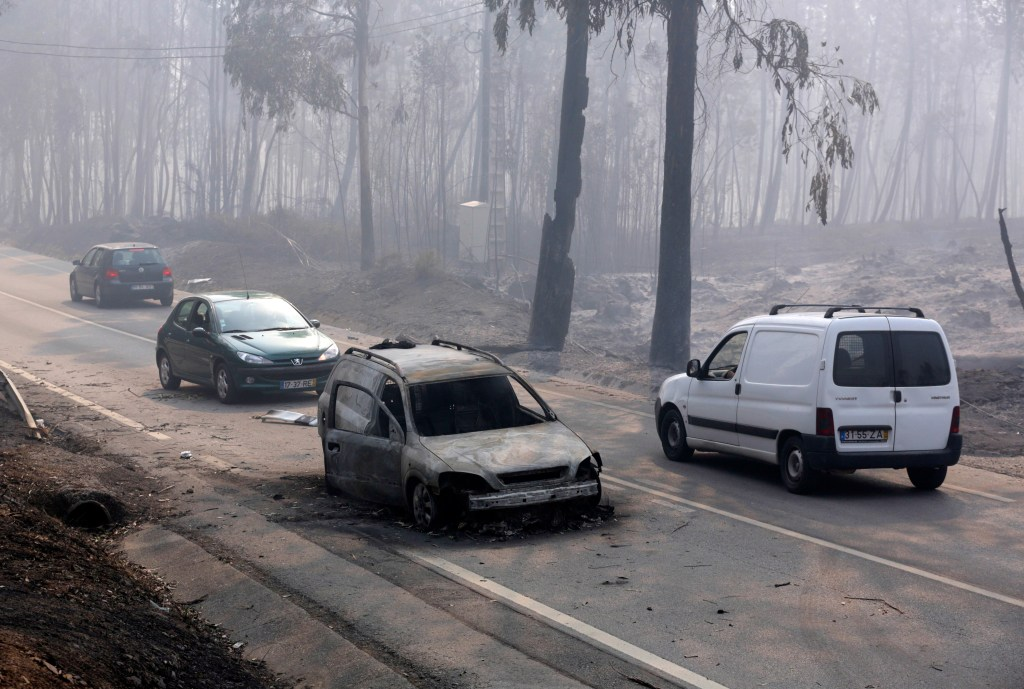 Cars drive past a burnt vehicle on the road between Castanheira de Pera and Figueiro dos Vinhos, central Portugal, on Sunday.