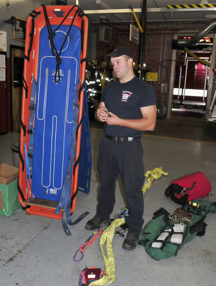 Skowhegan firefighter Scott Libby on Monday displays a Stokes basket and gear that he and firefighters from Skowhegan and Norridgewock used to rescue a Mercer man after he seriously cut his ankle with an ax on Sunday. It took about 300 feet of rope and 14 firefighters to haul him up from the riverside to the top of the steep embankment in a Stokes basket on Sunday.