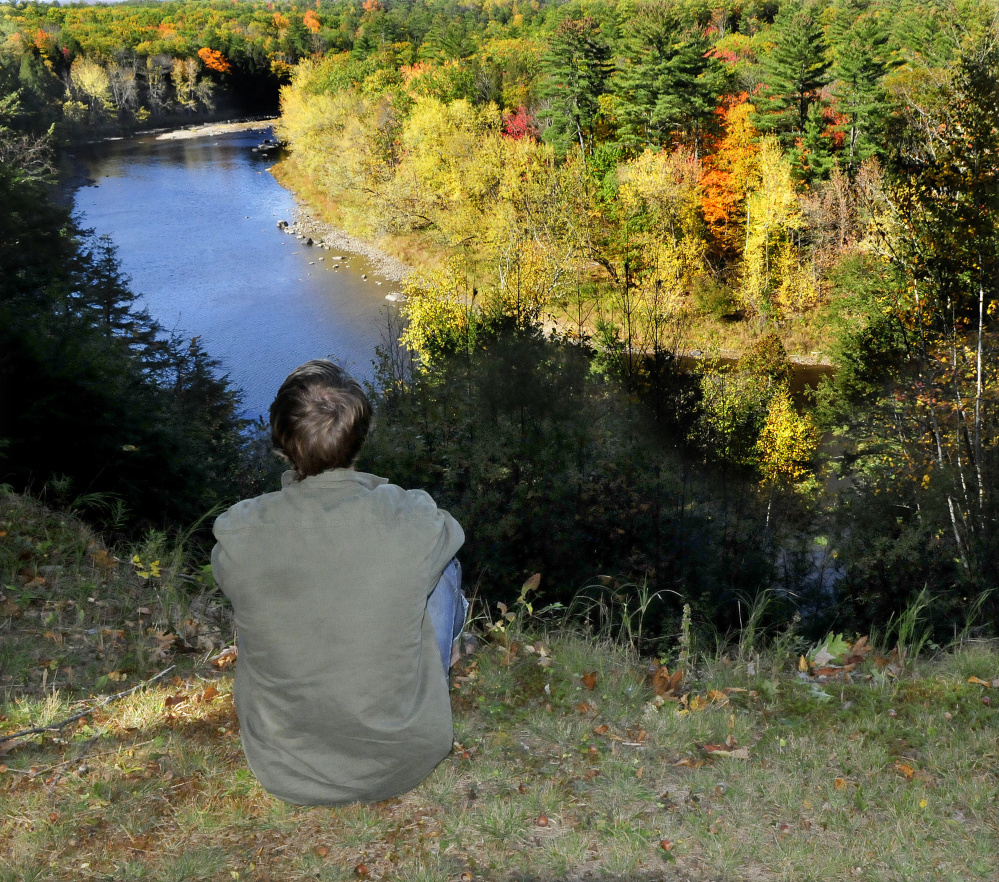 A Mercer resident who chose to remain anonymous looks down on the Sandy River from his home on Monday. He was rescued by firefighters from Skowhegan and Norridgewock after he injured his ankle with an ax. It took about 300 feet of rope and many hands to haul him up from the riverside to the top of the steep embankment in a Stokes basket on Sunday.