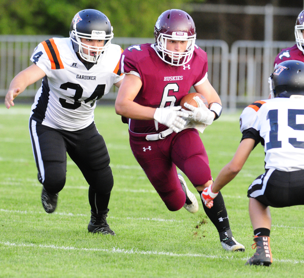 MCI's Adam Bertrand, center, gets chased down by Gardiner's Dylan Spencer, left, and Dimitri Paradis during an exhibition game Aug. 25 at Hoch Field in Gardiner.
