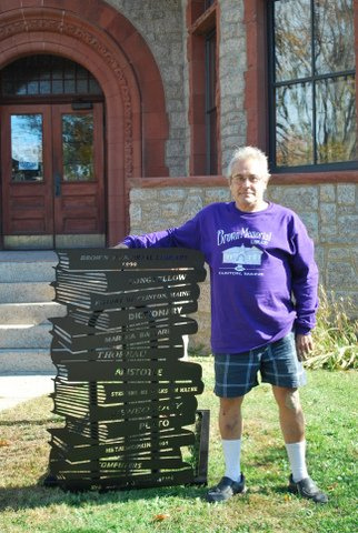 Bruce Keezer, president of the Friends of Brown Memorial Library in Clinton, with the new library-theme bike rack. The rack includes the titles Martha Ballard, history of Clinton and other local and Maine authors.