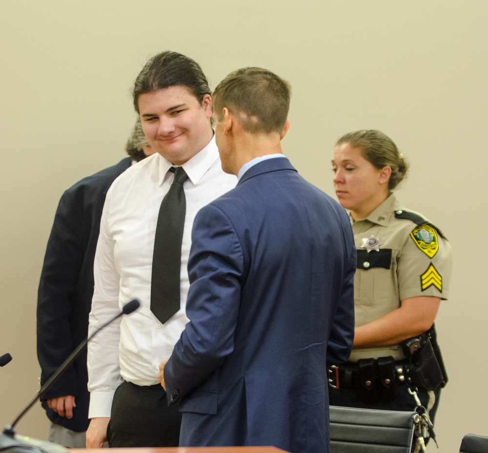 Andrew Balcer, left, smiles at his attorney, Walter McKee, at the end of a hearing Thursday at Capital Judicial Center in Augusta, where a judge will determine whether he should face trial on double murder charges as an adult.