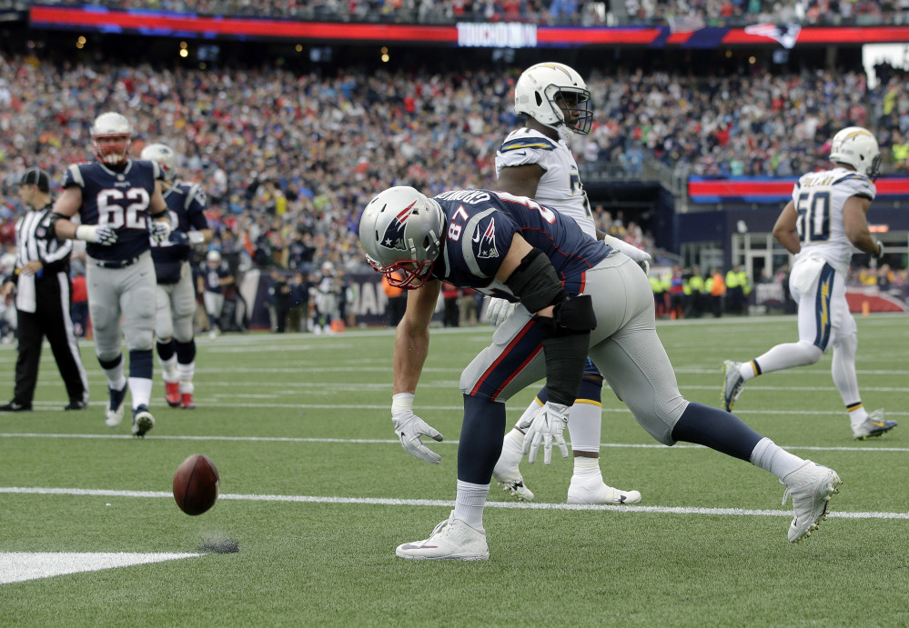 New England Patriots tight end Rob Gronkowski spikes the ball after catching a touchdown pass against the Los Angeles Chargers during the first half Sunday in Foxborough, Massachusetts.