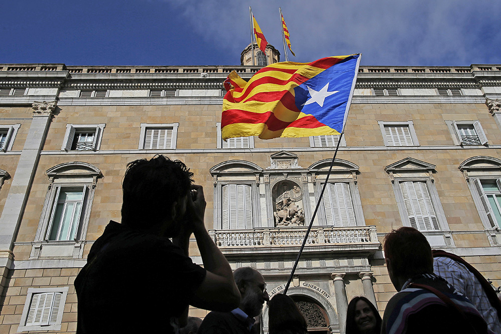 A man holds an independence flag outside the Palau Generalitat in Barcelona Monday. Catalonia's civil servants face their first full work week since Spain's central government overturned an independence declaration by firing the region's elected leaders. (AP Photo/Manu Fernandez)