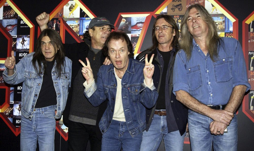 "The members of AC/DC, Malcolm Young, from left, Brian Johnson, Angus Young, Phil Rudd and Cliff Williams, pose in 2003 at the Apollo Hammersmith in London. Young, the rhythm guitarist and guiding force behind the bawdy hard rock band AC/DC who helped create such head-banging anthems as ""Highway to Hell,"" ""Hells Bells"" and ""Back in Black,"" was reported to have died in November. He was 64 and had suffered from dementia for years."