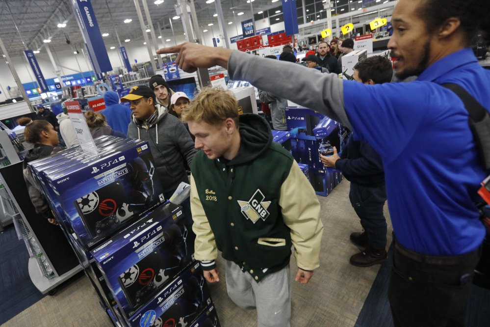 Shoppers rush into Best Buy as the doors open early Friday morning in Dartmouth, Mass.