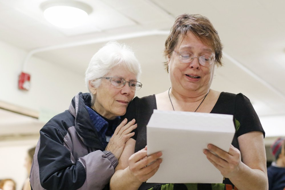 """Tirrell Kimball, left, of Falmouth hugs Alyson McLaughlin as she reads memories of her brother, Doug """"Digs"""" McLaughlin, written by Kimball's son, Stephen, who grew up with Doug."""