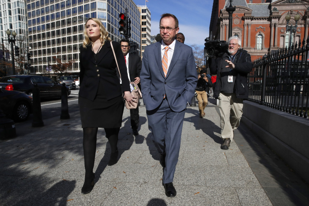 Mick Mulvaney walks to the Eisenhower Executive Office Building after leaving the Consumer Financial Protection Bureau  Monday. The judge's ruling letting him keep the acting director's position is not the final decision.