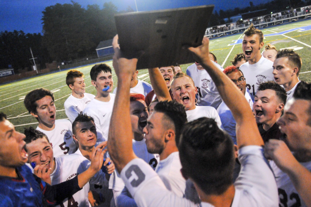 The Richmond boys soccer team celebrates with the plaque emblematic of the Class D South championship Thursday at McMann Field in Bath.