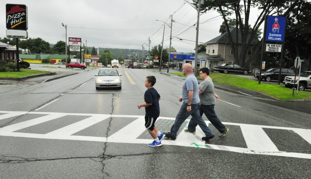 Jason Wyman, center and his sons Keygan, 10, left, and Ayden, 11, cross Western Avenue in this 2014 file photo in the cross walk where it intersects with Florence and Cushman streets. A forum set for Wednesday in Augusta will ask for input from pedestrians and others on ways to improve safety.