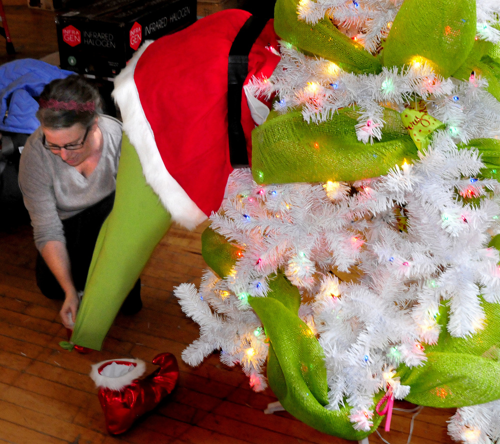 Tammy Richards places The Grinch on Tuesday inside a Christmas tree sponsored by Choice Investments for the upcoming Sukeforth Family Festival of Trees at the Hathaway Creative Center in Waterville.