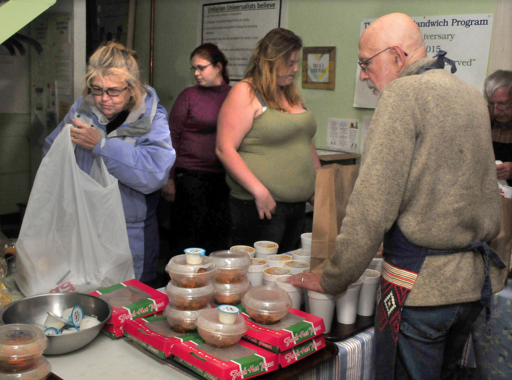 Recipients of the Unitarian Universalist Church Evening Sandwich program select food from volunteer Bruce O'Donnell at the church in Waterville on Tuesday. From left are Evonne Barter, Brittany Beech and Kathy Quimby.