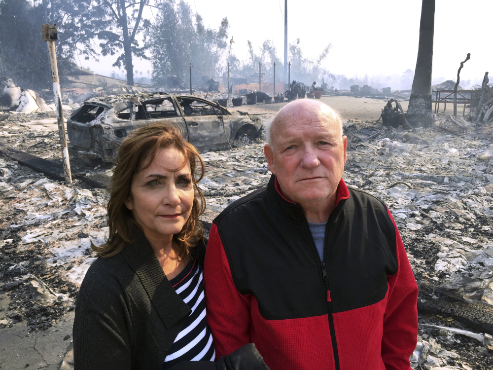 """Linda and John Keasler pose for a photo Tuesday in front of the ruins of their home at the Hawaiian Village Apartments, which was destroyed by fire. """"It is sad,"""" said John Keasler, 65."""" We loved this place. We lost everything."""""""