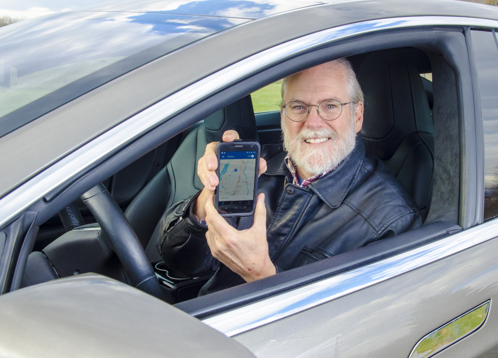 Scott Cowger holds up his phone with the Uber app on it Wednesday in his Tesla in Hallowell.