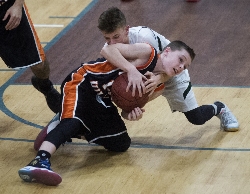 Temple's Micah Riportella, back, battles for the loose ball with Forest Hills' Parker Desjardins during a game last season in Waterville. The Bereans and Tigers lost some key players to graduation, but both return enough talent to stay in the playoff hunt.