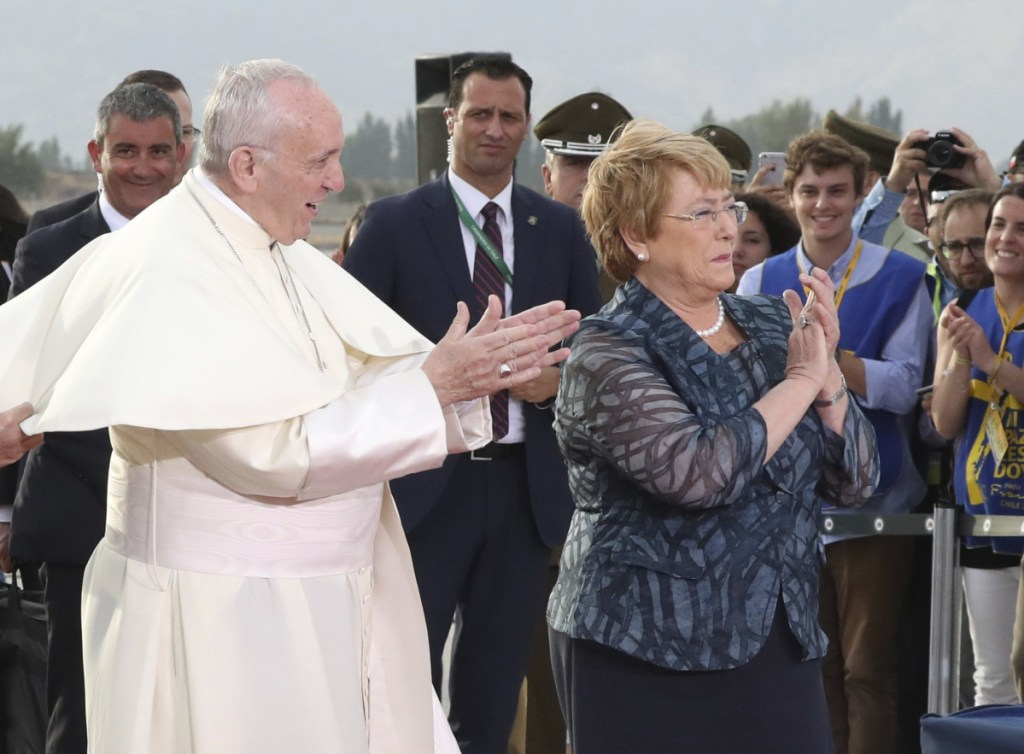 Pope Francis and Chile's President Michelle Bachelet applaud a group of young musicians as he arrives at the international airport in Santiago, Chile, on Monday.