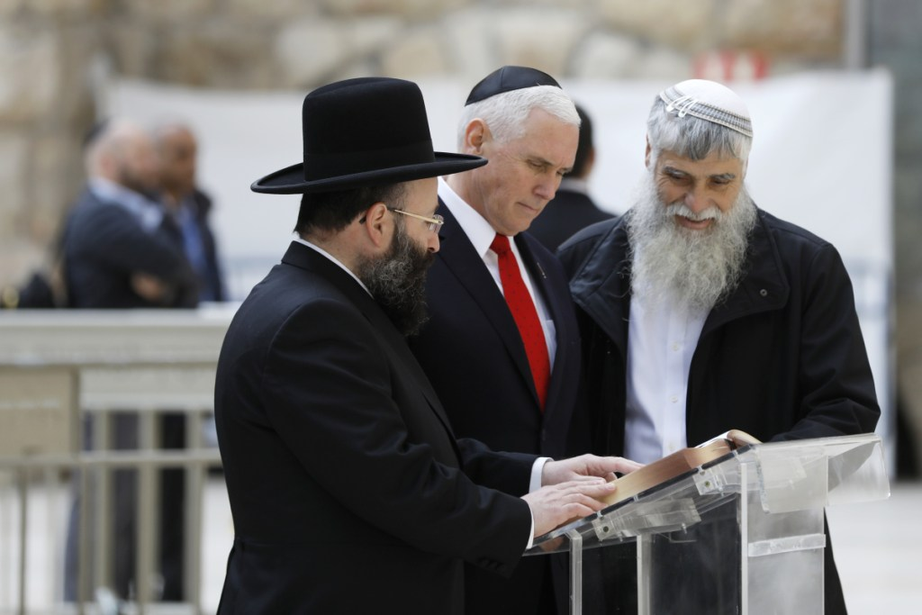 Vice President Mike Pence examines a book with Western Wall Heritage Foundation Director General Mordechai Elias, right, and Rabbi of the Western Wall Shmuel Rabinovitch during a visit to the Western Wall, Judaism's holiest prayer site, on Tuesday.