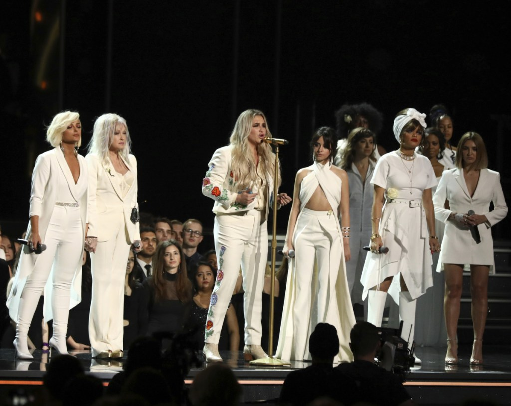 """Kesha, center, performs """"Praying"""" as, from left, Bebe Rexha, Cyndi Lauper, Camila Cabello, Andra Day and Julia Michaels look on at the 60th annual Grammy Awards on Sunday."""