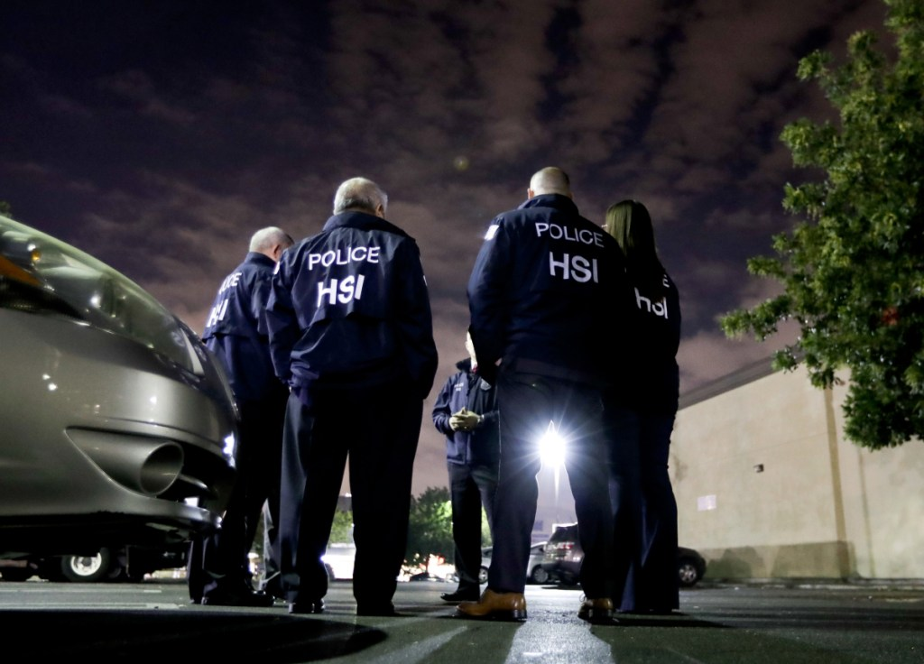 U.S. Immigration and Customs Enforcement agents gather Wednesday before serving a employment audit notice at a 7-Eleven convenience store in Los Angeles. Agents said they targeted about 100 7-Eleven stores nationwide Wednesday to open employment audits and interview workers.
