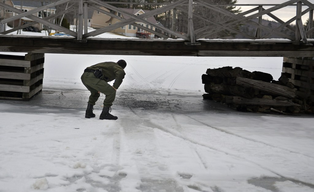District Game Warden Robert Decker on Sunday inspects a pier a snowmobile struck on a wooden bridge on Togus Pond in Augusta. Wardens are investigating the accident that seriously injured the 52-year-old male operator.