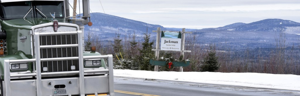 Trucks pass the Jackman town line sign on Monday, framed by mountains on U.S. 201.