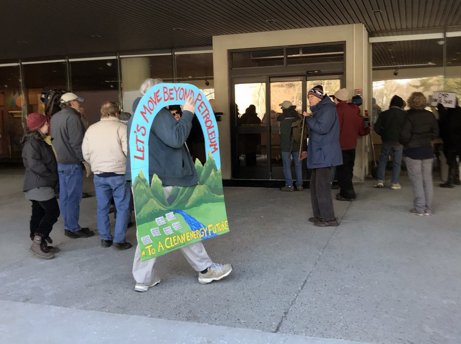 Protesters at the doors of Central Maine Power after being kept out of the lobby Monday.