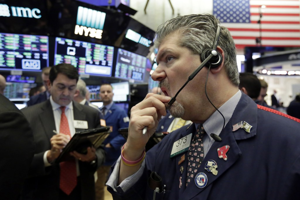 Trader John Panin, right, works on the floor of the New York Stock Exchange on Friday. Stocks struggled to stabilize Friday a day after the market entered its first correction in two years.