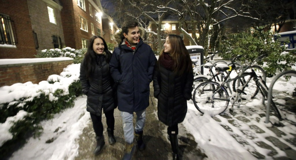 Brown University students from Puerto Rico, from left, Fabiola Guasp of San Juan, Andres Schiavone of Guaynabo, and Estefania Perez of Bayamon, walk back to their dormitory rooms after dinner in a cafeteria on the school's campus in Providence, R.I.
