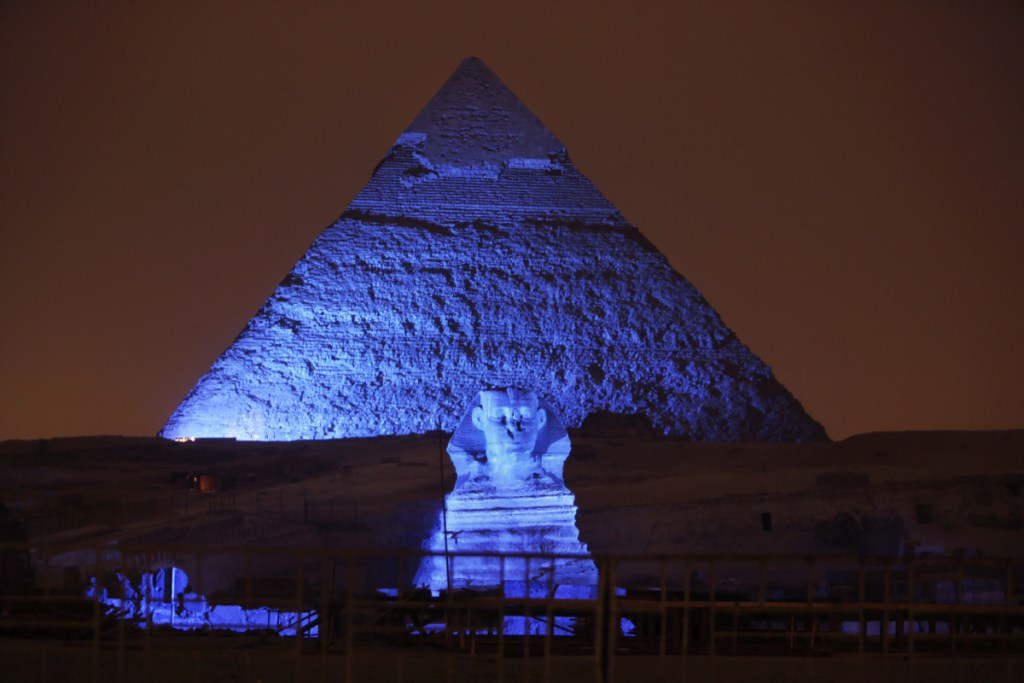 The Sphinx and the historical site of the Giza Pyramids are illuminated with blue light on Oct. 24, 2015, as part of the celebration of the 70th anniversary of the United Nations in Giza, just outside Cairo, Egypt. Archaeologists in Egypt say they have discovered a 4,400-year-old tomb near the pyramids outside Cairo. Egypt's Antiquities Ministry announced the discovery Saturday and said the tomb likely belonged to a high-ranking official known as Hetpet during the 5th Dynasty of ancient Egypt.