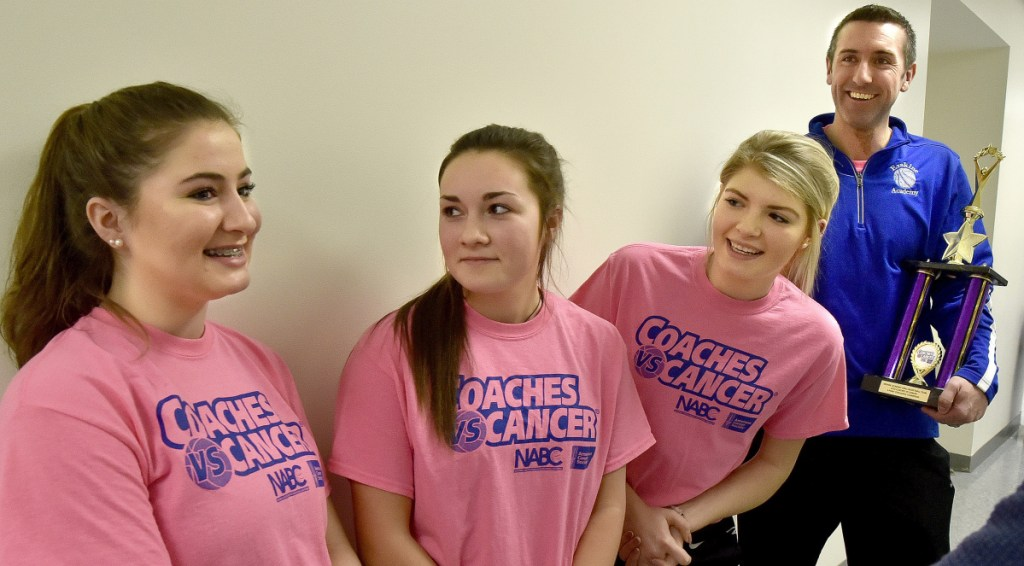 Erskine Academy girls basketball players Lydia Boucher, left, Lauren Wood, middle, Bailey Cloutier and coach Mitch Donar, right, speak about the team and community efforts in raising $10,000 for the American Cancer Society during a ceremony Tuesday at the South China school.