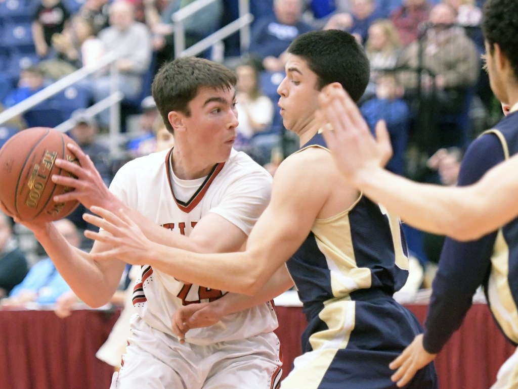 Hall-Dale's Owen Dupont, left, looks for an opening through Traip defenders during a Class C South quarterfinal game at the Augusta Civic Center.