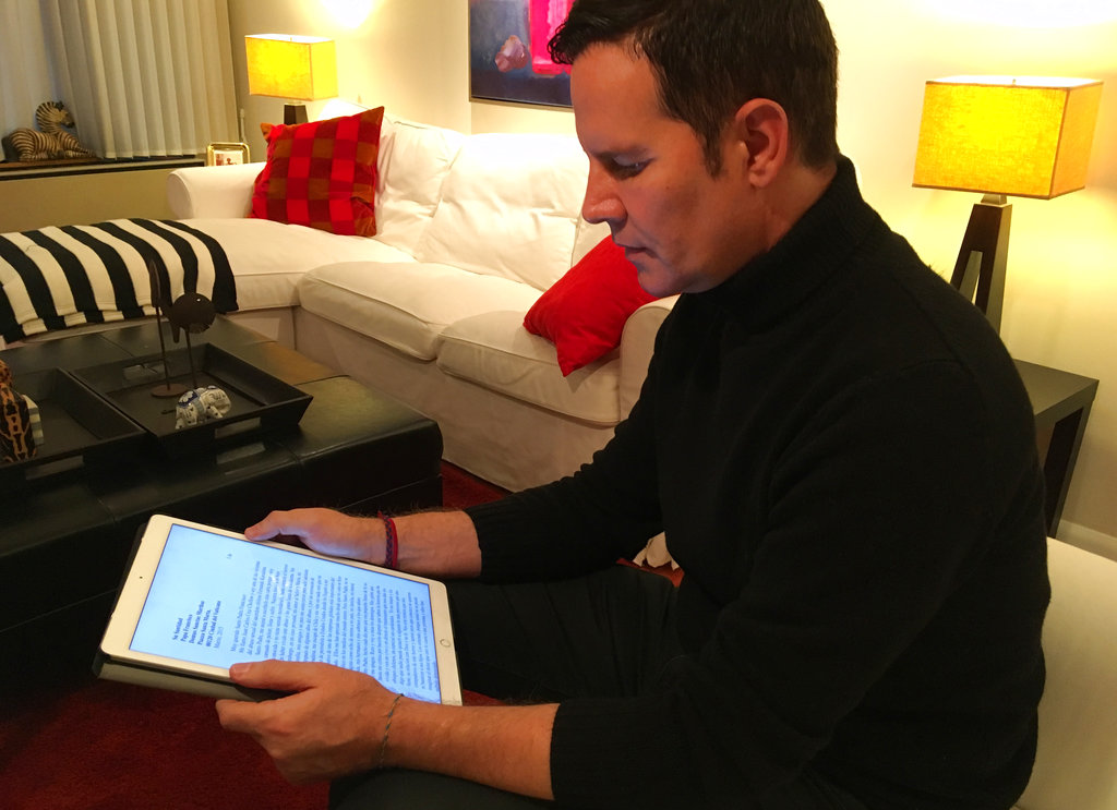 Juan Carlos Cruz reads from his tablet during an interview with The Associated Press in Philadelphia, Sunday. Cruz says Pope Francis received a letter he wrote in 2015 detailing the sexual abuse he suffered at the hands of a priest and efforts by the Chilean church to cover it up, contradicting the pope's recent insistence that no victims had come forward.
