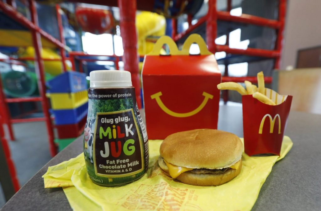 A Happy Meal featuring non-fat chocolate milk and a cheeseburger with fries are arranged for a photo at a McDonald's restaurant. McDonald's will soon remove cheeseburgers and chocolate milk from its Happy Meal menu.