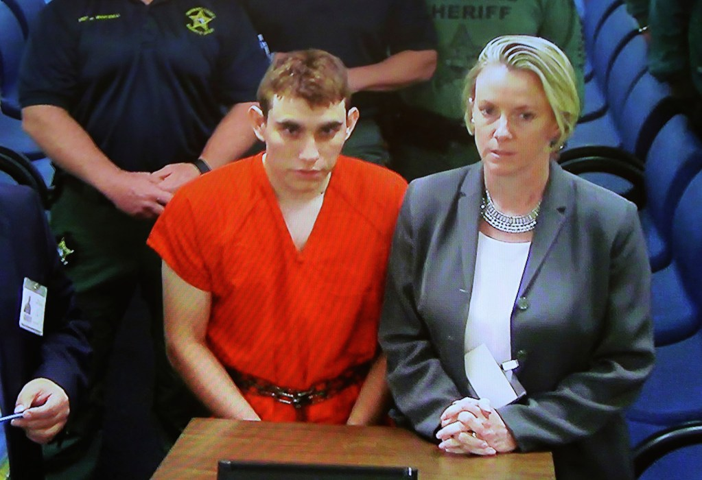 A video monitor shows school shooting suspect Nikolas Cruz, left, making an appearance in Broward County Court in Fort Lauderdale, Florida. Cruz is accused of opening fire at a high school in Parkland, killing least 17 people.